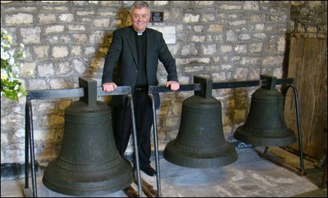 Rev Keith Evans with the three bells at All Saints Church in Mumbles