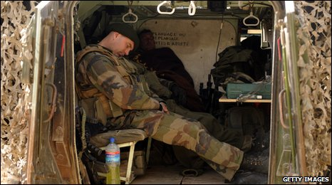 A French soldier sleeps in a military vehicle