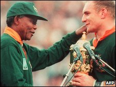 Springbok captain Francois Pienaar (R) receives the Rugby World Cup from South african President Nelson Mandela at Ellis Park in Johannesburg (24 June 1995)