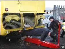 Workers examine the bus on Monday