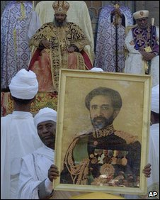 Ethiopian Orthodox priests hold the image of late Emperor Haile Selassie atop a casket containing his remains at the beginning of a ceremony Sunday 5 November 2000 in Addis Ababa to rebury him 25 years after his death while under house arrest, Ethiopian Patriarch Paulus sits in the background