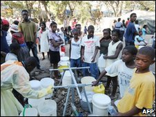 People queue up for drinkable water in Port-au-Prince on 8 February
