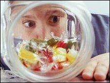 Child looking through a jar of sweets