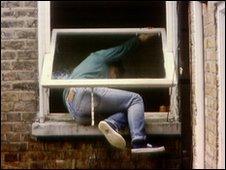 Man climbing through a window