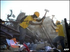 Workers demolish a building damaged in the 12 January earthquake in Port-au-Prince, Haiti