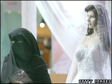 An Emirati woman wearing a niqab walks past a mannequin at a bridal wear show in Dubai, April 2007