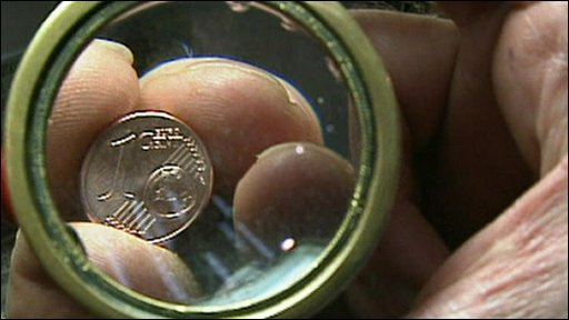 A euro coin behind a magnifying glass