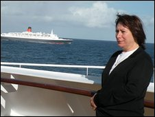 Barbara Gregory seen posing on the QM2 with the QE2 in the background