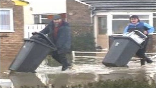 Men move wheelie bins in flood water
