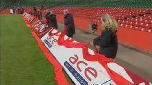 Staff from Radio Wales drape the red scarf around the stadium pitch