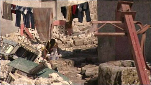 A woman washes clothes among the rubble in Leogane, Haiti
