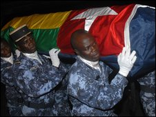 The coffin of one of those killed is carried by Togolese policemen