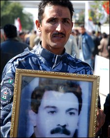 Man with picture of a relative killed by the Baath regime