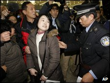 Airport security staff move Feng Zhenghu's supporters in Shanghai, China (12 Feb 2010)