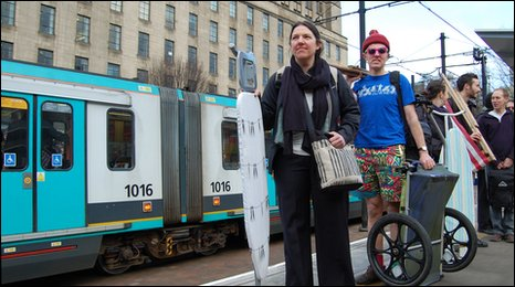 cycling campaigners wait for a tram with ironing boards and deckchairs