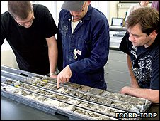 Scientists examine a core sample (Image: Ecord-IODP)