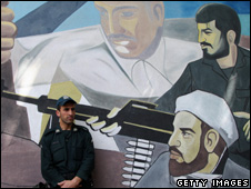A member of the Revolutionary Guard stands by a mural depicting the 1979 Iranian Revolution