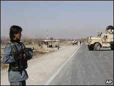 An Afghan police officer stands near the site of a suicide attack in Kandahar, southern Afghanistan, 13 February 2010