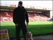 Police officer and dog at stadium