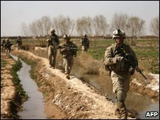 US marines with 1/3 marine Charlie Company walk along poppy field irrigation canals in Trikh Nawar