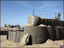 A Nato soldier puts barbed wires on top of the protective walls around a newly setup joint Afghan and Nato base in Marjah on 18 Feb 2010