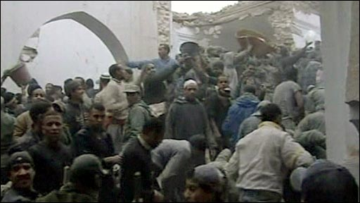Crowd of people trying to sift through the rubble after a minaret collapsed