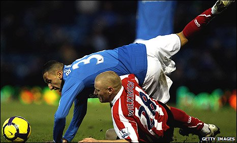 Belhadj of Portsmouth clashes with Andy Wilkinson of Stoke