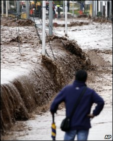 A resident looks on as flood waters create a canal in downtown Funchal, Madeira