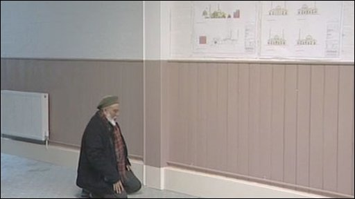 A Muslim man praying next to plans for a new mosque near Sandhurst