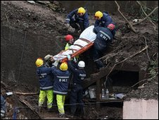 Rescue teams remove a body from a house wrecked in a landslide in Madeira 22/02/10