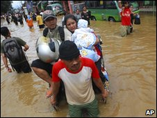 Indonesians wade through flood in Bandung, West Java, on 19 Feb 2010