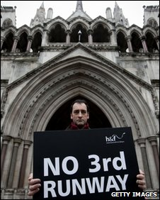 Comedian Alistair McGowan holds a placard outside the High Court