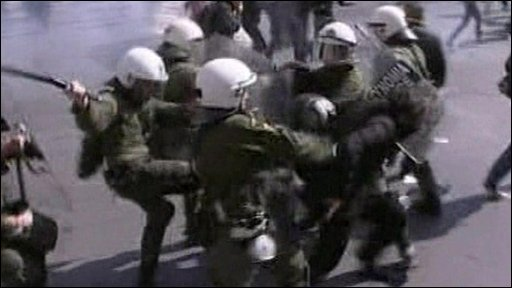 Police use batons against a protester in Greece