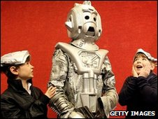 Charlie Sheaf 11, and sister Sophie Sheaf 12, stands beside a Cyberman costume