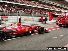 Fernando Alonso's Ferrari is towed back to the pits after stopping on the track with an electronic failure
