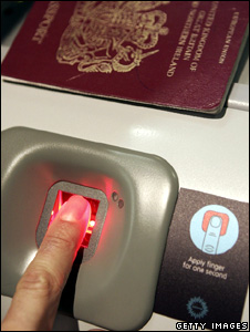 A man has his fingerprint scanned on a biometric check-in kiosk in the UK (2006)