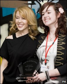 Kylie Minogue with student Emma McGann and award
