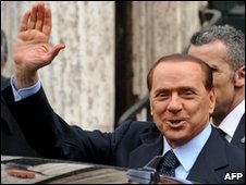 Italian Prime Minister Silvio Berlusconi waves as he leaves a memorial Mass for his mother in Rome, 26 February