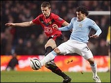 United's Michael Carrick and City's Carlos Tevez contest possession