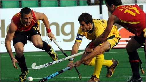 Spanish hockey players Roc Oliva (L) and Albert Sala (R) stops South African hockey player Austin Smith (C)