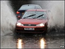 A car drives through deep water after heavy rain caused local flooding in Essex