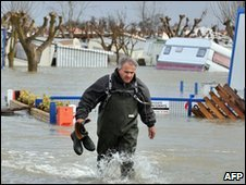 A man walks though a flooded campsite in La Faute-sur-Mer, western France