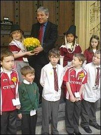 Llefarydd Ty'r Cyffrein, John Bercow, yn derbyn tusw o Gennin Pedr gan ddisgyblion Ysgol Gymraeg Llundain.