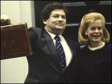 Nigel Lawson holding up the budget box, standing outside number 11 with his wife