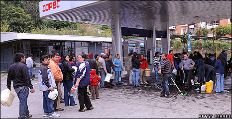 People queue at a petrol station in Concepcion, Chile