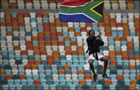 A man holds a South African flag as he glides in the air through the Moses Mabhida Stadium on a harness in Durban, South Africa