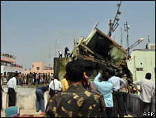 Residents and rescuers search the wreckage of a building in Hyderabad on March 3, 2010