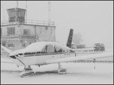 snow grounds an aeroplane on an airport runway