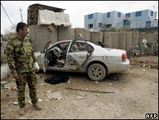 A solider stands beside the wreckage of a car at the site of a suicide bombing in Baquba (3 March 2010)