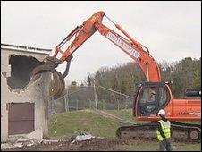 Bulldozer demolishing house